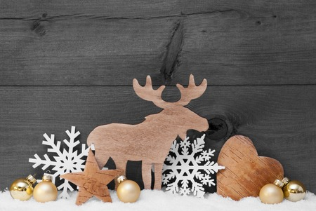 Christmas Card With Golden Festive Decoration On Snow. White Moose, Christmas Ball, Hear, Snowflake, Star. Gray, Rustic, Vintage Wooden Background. Copy Space For Advertisement. Black And White Image Standard-Bild