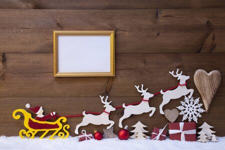 santa moose: Christmas Decoration, Red Santa Claus, Yellow Sled And Reindeer On White Snow. Gift, Present, Christmas Tree, Ball, Snowflakes, Heart, Picture Frame. Brown Rustic Vintage Wooden Background, Copy Space