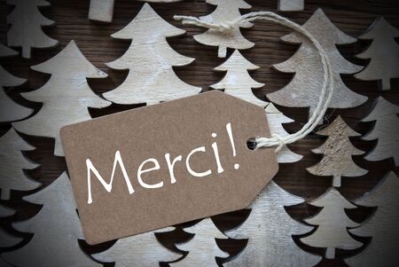 french text: Brown Christmas Label With Ribbon On Wooden Christmas Trees Background. Vintage Style. Label With French Text Merci Means Thank  You For Christmas Or Season Greetings.Close Up Or Macro Stock Photo