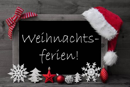 free backgrounds: Black And White Blackboard With Red Santa Hat And Christmas Decoration like Snowflake, Tree, Christmas Ball, Fir Cone, Star. German Text Weihnachtsferien Means Christmas Holiday. Wooden Background