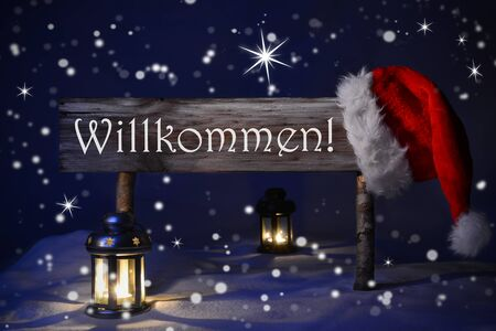 willkommen: Wooden Christmas Sign And Santa Hat With Snow Snowy Scenery. German Text Willkommen Means Welcome For Seasons Greetings. Blue Silent Night With Snowflakes And Sparkling Stars. Lantern And Candlelight