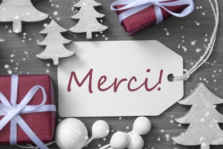 french text: Black and White Close Up Of Label With Ribbon,Red Gift,Present, Ribbon And Tree With Snowflakes. Christmas Decoration Or Card On Wooden Background. French Text Merci Means Thank You