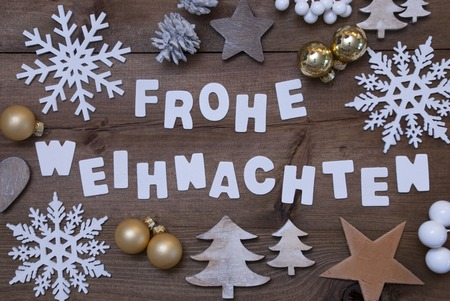 frohe: White Letters With German Frohe Weihnachten Means Merry Christmas On Brown Wooden Background. Rustic, Vintage Style. Christmas Decoration, Christmas Tree, Snowflakes,Golden Christmas Ball