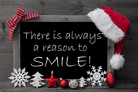 black and white cone: Black And White Blackboard With Red Santa Hat And Christmas Decoration like Snowflake, Tree, Christmas Ball, Fir Cone, Star. English Quote There Is Always A Reason To Smile. Wooden Background