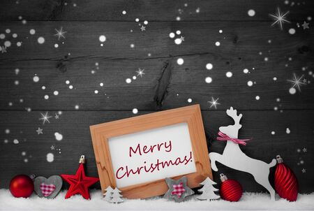 like english: Gray Christmas Card With Picture Frame On White Snow, Snowflakes And Stars. English Text Merry Christmas. Red Christmas Decoration Like Ball, Tree And Reindeer. Wooden Background. Black And White