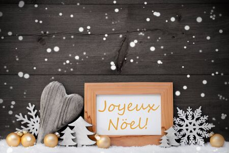christmas time: Golden Decoration On Snow. Heart, Christmas Tree Balls, Snowflakes, Christmas Tree,Picture Frame.French Joyeux Noel Mean Merry Christmas. Rustic, Vintage Gray Wooden Background. Black And Withe