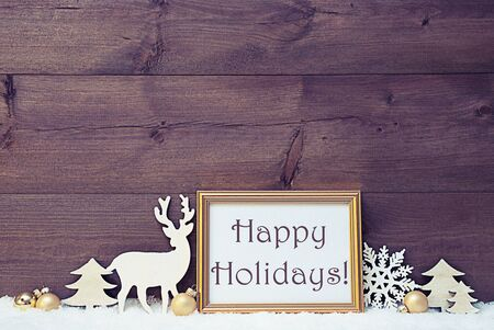 like english: Vintage Christmas Card With Picture Frame On White Snow. English Text Happy Holidays. White Decoration Like Snowflake, Tree, Golden Balls And Reindeer. Shabby Chic, Wooden Background