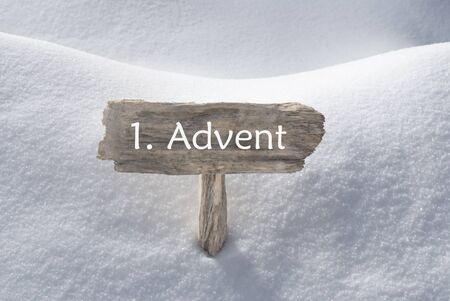 free sign: Wooden Christmas Sign With Snow In Snowy Scenery. German  Text 1 Advent Means Christmas Time For Seasons Greetings Or Christmas Greetings. Christmas Atmosphere.