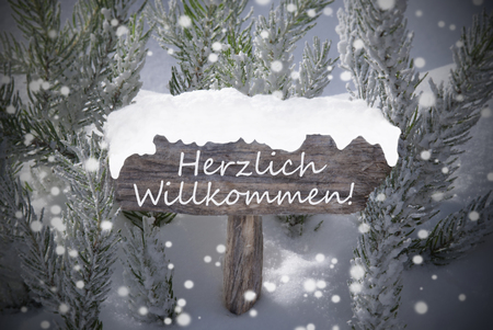 willkommen: Wooden Christmas Sign With Snow And Fir Tree Branch In The Snowy Forest. German Text Herzlich Willkommen Means Welcome For Seasons Greetings Or Christmas Greetings. Christmas Atmosphere With Snowflake Stock Photo