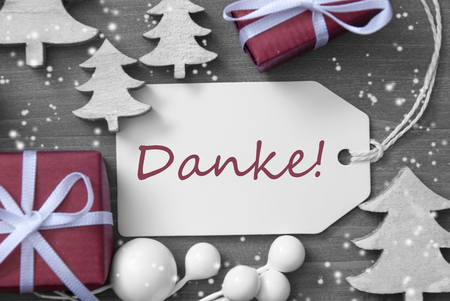 christmas time: Black and White Close Up Of Label With Ribbon,Red Gift,Present, Ribbon And Tree With Snowflakes. Christmas Decoration Or Card On Wooden Background. German Text Danke Means Thank You