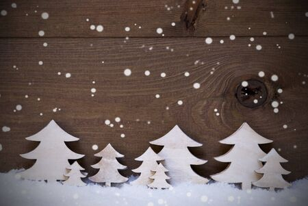 White Wooden Christmas Trees On Snow, Snowflakes. Christmas Decoration Or Christmas Card. Brown, Rustic, Vintage Background With Copy Space For Advertisement Or Seasons Greetings.