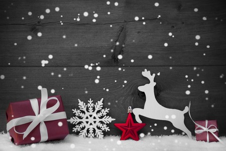 Weihnachtskarte mit rotem festliche Dekoration auf weißen Schnee. Geschenk, Geschenk, Rentier, Weihnachtsball, Schneeflocken. Brown, Rustikal, Weinlese-Holz-Hintergrund. Kopieren Sie Platz für Werbung. Schwarz und Weiß