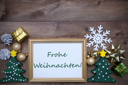 frohe: Golden Picture Frame With Green Tree And Decoration Like Gifts, Balls And Snowflake. German Text Frohe Weihnachten Means Merry Christmas. Brown Wooden And Rustic Retro Background As Christmas Card.