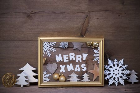 like english: Golden Picture Frame With White Christmas Decoration Like Christmas Tree And Snowflake. English Text Merry Xmas. Vintage Wooden And Rustic Retro Background. Christmas Card For Seasons Greetings