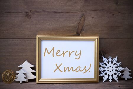 like english: Golden Picture Frame With White Christmas Decoration Like Christmas Tree And Snowflake. English Text Merry Xmas. Vintage Wooden And Retro, Rustic Background. Christmas Card For Seasons Greetings