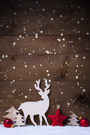Vertical Christmas Card With White And Red Christmas Decoration On Snow And Snowflakes. Copy Space For Advertisement. Decoration Like Balls, Tree And Reindeer. Vintage, Rustic Wooden Background. Standard-Bild