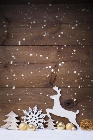 Verticale Kerstkaart met witte en gouden kerst versiering op sneeuw. Kopie Ruimte Voor Reclame. Decoratie als sneeuwvlokken, ballen, boom en rendier. Vintage, rustieke houten achtergrond.