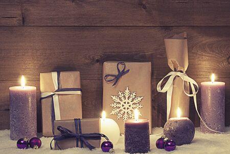 Tarjeta de Navidad del vintage de decoración o de púrpura velas, regalos de Navidad, regalos, bolas de navidad, copo de nieve y nieve. Ambiente Tranquilo Con luz de las velas. Shabby Chic Fondo De Madera