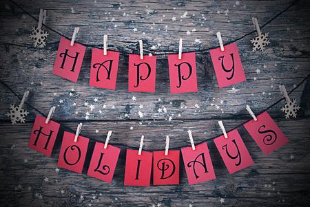 animados: Vintage O Shabby Chic fondo rústico de madera. Etiquetas rojas con buenas fiestas colgando de una línea. Los copos de nieve que cuelga en paño Clavijas. Tarjeta de Navidad para saludos de las estaciones. Marco Para Estilo Noche