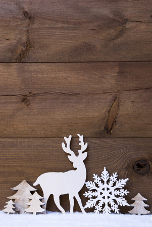wooden reindeer: Vertical Christmas Card With White Christmas Decoration On Snow. Copy Space For Advertisement. Decoration Like Snowflake, Tree And Reindeer. Vintage, Rustic Wooden Background. Stock Photo