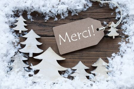 french text: Brown Christmas Label With Ribbon On Wooden  Background With White Christmas Trees And Snow. Vintage Style. Label With French Text  Merci Means Thank You For Christmas Or Season Greetings