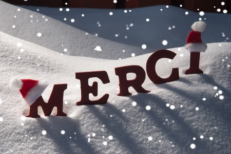 french text: Red Letters With Santa Hat On White Snow With Snowflakes As Christmas Card.  French Text Or Word Merci Mean Thank  You. Snowy Scenery And Atmosphere. Rustic Vintage Wooden Background
