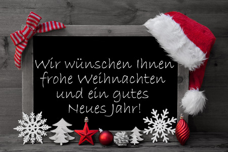 Black And White Blackboard With Red Santa Hat And Christmas Decoration like Snowflake, Tree, Christmas Ball, Fir Cone, Star. German Text Danke Means Thank You. Wooden Background