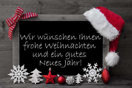 Schwarzweiß-Tafel mit rotem Sankt-Hut und Weihnachtsdekoration wie Schneeflocke, Baum, Weihnachtskugel, Tannenzapfen, Stern. Deutsch Text Danke Means Danke. Holzuntergrund Standard-Bild - 45908572