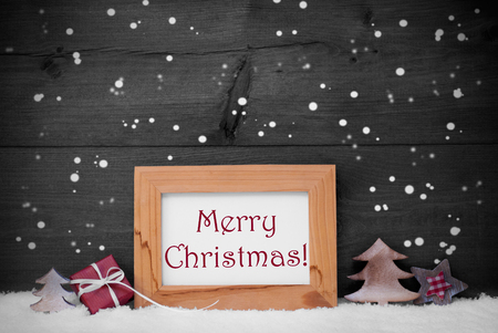 red star: Gray Christmas Card With Brown Picture Frame On White Snow With Snowflakes. Red English Text Merry Christmas, Tree, Christmas Gift And Star. Rustic Wooden, Retro Vintage Background. Black And White Stock Photo
