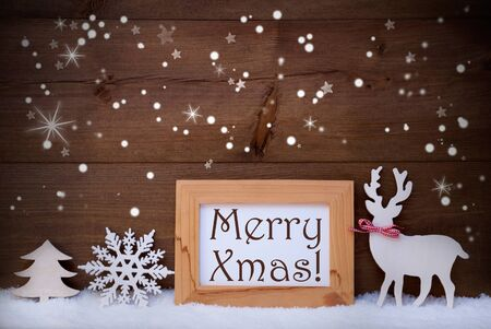 like english: Christmas Card With Picture Frame On Snow, Snowflakes And Sparkling Stars. English Text Merry Xmas. White Christmas Decoration Like Snowflake, Tree And Reindeer. Wooden And Vintage Background