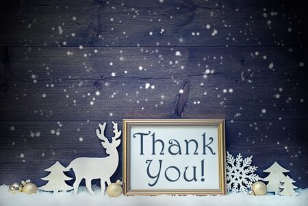 like english: Vintage Christmas Card With Picture Frame On White Snow. English Text Thank You. White Decoration Like Snowflakes, Tree, Golden Balls And Reindeer. Shabby Chic, Wooden Background By Night