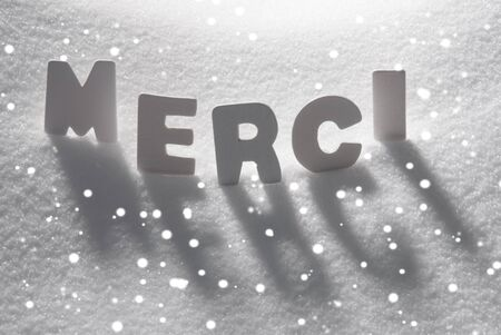 merci: White Letters Building French Text Merci Means Thank You On White Snow. Snowy Landscape Or Scenery With Snowflakes. Christmas Card For Seasons Greetings Or Usable As Background.