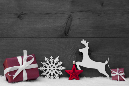 Christmas Card With Red Festive Decoration On White Snow. Gift, Present, Reindeer, Christmas Ball, Snowflakes. Brown, Rustic, Vintage Wooden Background. Copy Space For Advertisement. Black and White