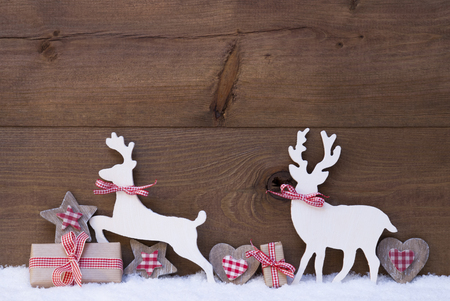 Christmas Decoration With Reindeer Couple In Love On White Snow. Christmas Gift, Present, Red Ribbon, Heart, Star. Brown, Rustic, Vintage Wooden Background. Christmas Card For Seasons Greetings Stock Photo