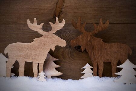 realtionship: Christmas Decoration, Moose Couple In Love On White Snow And Christmas Tree. Rustic, Vintage Wooden Background. Christmas Card For Seasons Greetings. Stock Photo