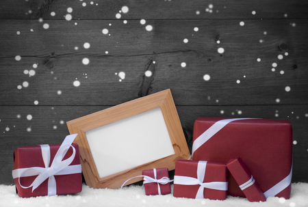 black picture frame: Red, Gray Christmas Decoration On Snow, Snowflakes, Christmas Gifts, Presents. Picture Frame. Copy Space For Advertisement. Rustic, Vintage Wooden Background. Festive Snowy Card. Black And White Image Stock Photo
