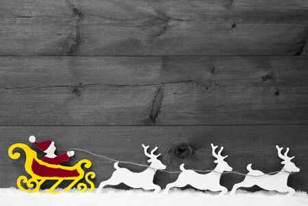 santa moose: Christmas Decoration, Red Santa Claus With Yellow Sled And White Reindeer On Snow. Brown Vintage Wooden Background With Copy Space. Gray Christmas Card For Seasons Greetings. Black And White Image Stock Photo