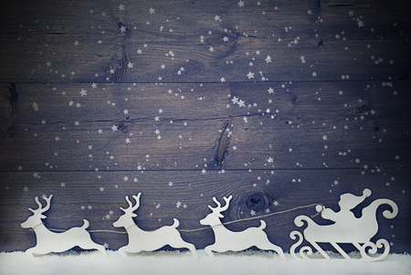 Gray Vintage Christmas Decoration, White Santa Claus With Sled And Reindeer On Snow. Brown Shabby Chic Wooden Background With Copy Space, Snowflakes And Stars. Christmas Card For Seasons Greetings Standard-Bild