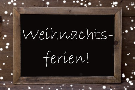 greeting season: Brown Blackboard With German Text Weihnachtsferien Means Christmas Holiday As Greeting Card. Wooden Background. Vintage Rustic Style. Snowflakes Symbolizing Christmas Or Winter Season.