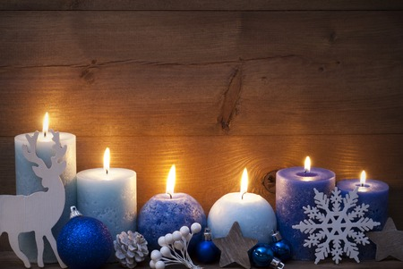 Christmas Decoration With Purple And Blue Candles,Reindeer, Christmas Ball, Snowflake, Fir Cone,Star. Peaceful Atmosphere With Candlelight. Wooden Background For Copy Space. Vintage Style