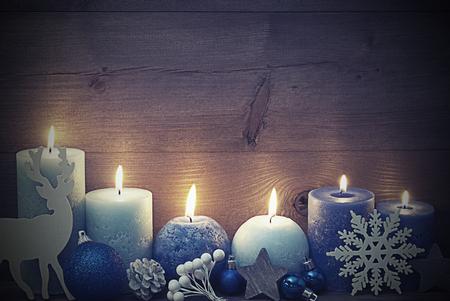Shabby Chic, Vintage-Chirstmas Dekoration mit lila und blaue Kerzen, Rentier, Weihnachtsball, Schneeflocke, Tannenzapfen, Stern. Ruhige Atmosphäre mit Kerzenlicht. Hölzerner Hintergrund für Textfreiraum