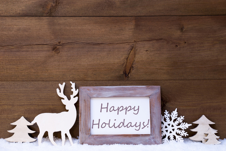 like english: Christmas Card With Shabby Chic Picture Frame On White Snow. English Text Happy Holidays. Christmas Decoration Like Snowflake, Tree And Reindeer. Vintage, Wooden Background.