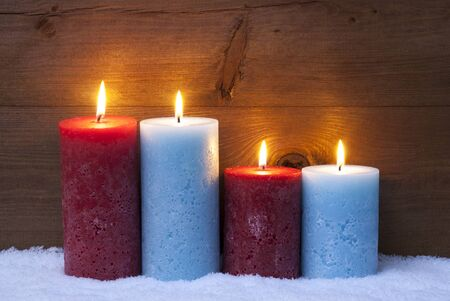 candlelight: Christmas Decoration With Red And Blue Candles. Four Candle For Advent Or Christmas Time. Peaceful, Romantic Atmosphere With Candlelight. Brown Wooden Background For Copy Space. Vintage Rustic Style