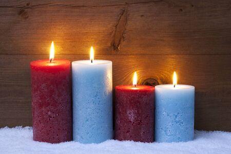 luz de velas: Decoraci�n de Navidad con velas rojas y azules. Cuatro vela para ADVENT o el tiempo de Navidad. Pac�fica, ambiente rom�ntico con velas. Fondo de madera de color marr�n para copiar el espacio. Estilo r�stico de la vendimia Foto de archivo