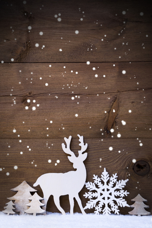 Vertical Christmas Card With White Christmas Decoration On Snow And Snowflakes. Copy Space For Advertisement. Decoration Like Snowflake, Tree And Reindeer. Vintage, Rustic Wooden Background By Night