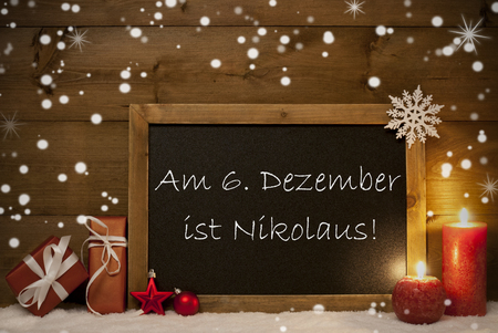 st german: Festive Christmas Card With Chalkboard, Red Gifts, Balls, Snowflakes And Candles. Christmas Decoration With Vintage Wooden Background. German Text Am 6 Dezember Ist Nikolaustag Mean St Nicholas Day Stock Photo