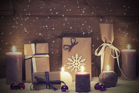 shabby chic background: Vintage Christmas Card Or Decoration With Purple Candles, Christmas Gifts, Presents, Christmas Ball, Snowflake, Snow And Sparkling Stars. Peaceful Atmosphere With Candlelight. Shabby Chic Background
