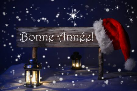 french text: Wooden Christmas Sign And Santa Hat With Snow. French Text Bonne Annee Means Happy New Year For Seasons Greetings. Blue Silent Night With Snowflakes And Sparkling Stars. Lantern And Candlelight
