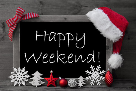 like english: Black And White Blackboard With Red Santa Hat And Christmas Decoration like Snowflake, Tree, Christmas Ball, Fir Cone, Star. English Text Happy Weekend. Wooden Background