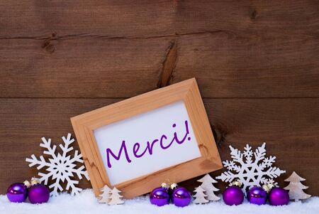 french text: Purple Christmas Decoration On Snow. Christmas Tree Balls, Snowflake And Christmas Tree. Picture Frame With French Text Merci Means Thank You. Rustic, Vintage Brown Wooden Background.
